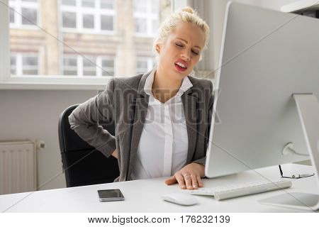 Woman with back pain sitting by the computer at the office