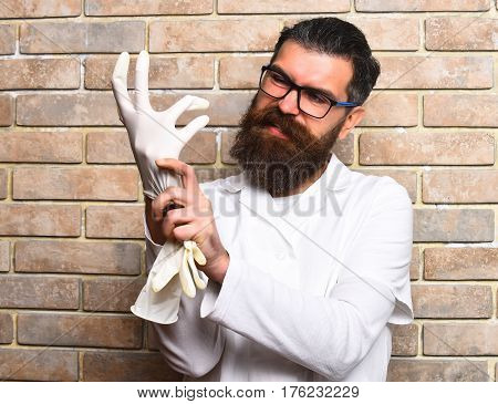 Bearded man long beard. Brutal caucasian doctor or unshaven hipster postgraduate student in medical gown and glasses wearing gloves on beige brick wall studio background. Medicine concept