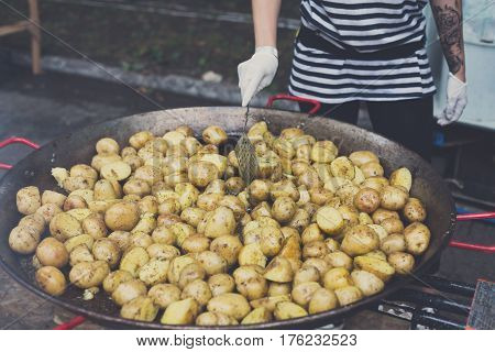 Country fair, vendor cooking. Roasted potatoes cooked outdoors in big metal cauldron pot. Cookout vegetable meals. Fresh organic snack, potatoes cooked on grill flame. Street fast food.