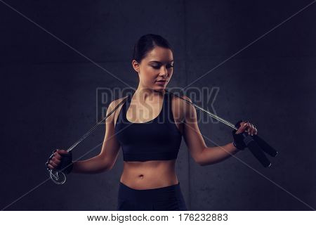 sport, fitness, training, stamina and people concept - young sporty woman with jumping rope