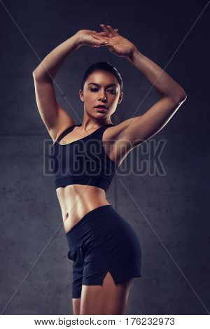 sport, fitness, bodybuilding, weightlifting and people concept - young woman posing and showing muscles in gym