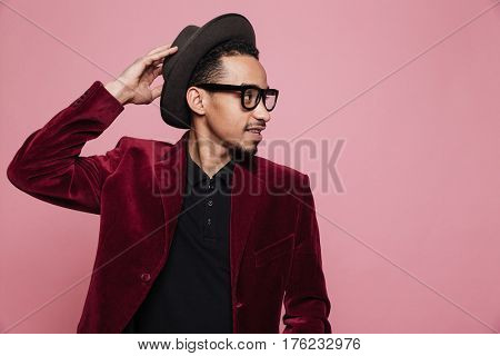 Portrait of a stylish afro american man in hat and eyeglasses posing with his hand on hat isolated on the pink background