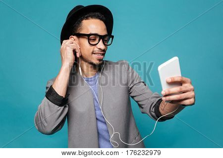 Portrait of a happy young african man listening music with earphones and phone over blue background