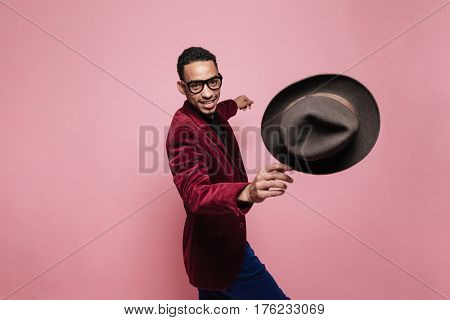 Portrait of a smiling afro american man in jacket throwing hat isolated over pink
