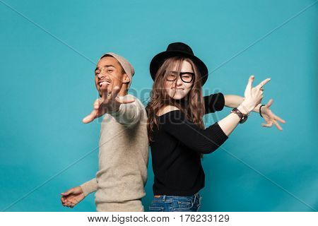 Portrait of a cheerful young couple dancing and having party over blue background