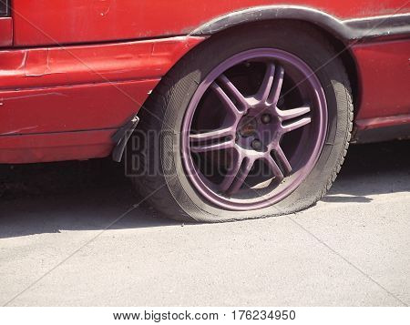 Dirty old red car tire break deflated