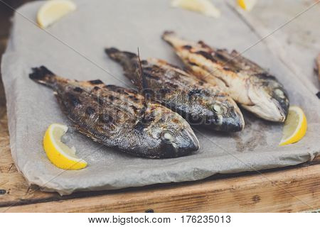 Plenty of dorado fish grilled at barbecue. Seafood bbq outdoors at picnic, party. Street food, take away on big tray. Grill crispy roasted fish with lemon