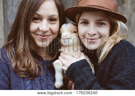 Friends having fun with baby goat