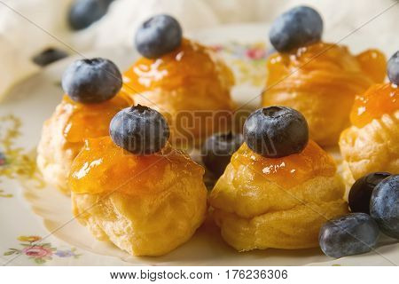French Traditional Dessert. Profiteroles With Blueberry And Apri