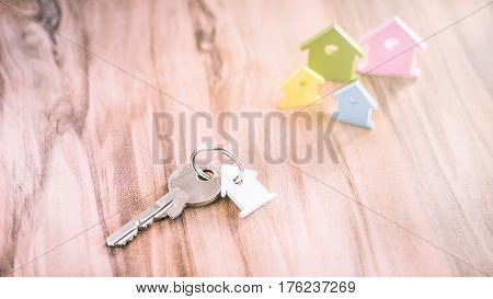 Silver Key with Breloque in Form of House on Vhain with some Miniature Symbol of Houses on Side in Different Colours on Wooden Surface.
