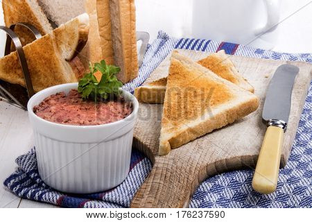 pork liver sausage with parsley and sliced toast bread on wooden board