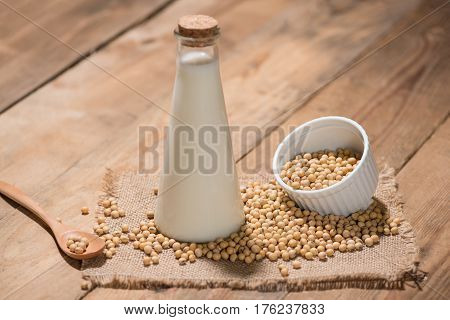A bottle of soy milk or soya milk and soy beans on wooden table.