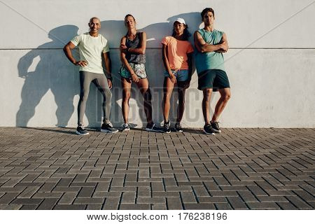 Fitness Group Posing By A Wall Outdoors