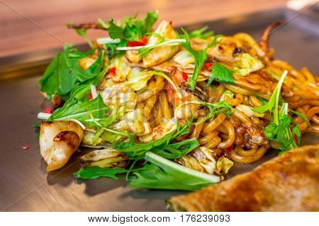 Japanese yakisoba noodles with seafood grilled on the iron griddle called teppanyaki