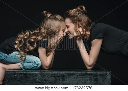 Side View Of Stylish Daughter And Mother Smiling, Touching Foreheads And Looking At Each Other On Bl