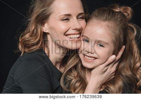 Portrait Of Stylish Daughter And Mother Smiling And Hugging On Black