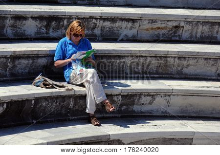 KOS ISLAND GREECE - OCTOBER 03 2014: Caucasian woman reads a guide-book on the steps of the ancient theater