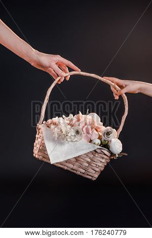 Partial View Of Mother And Daughter Holding Basket With Flowers On Black