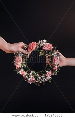 Partial View Of Mother And Daughter Holding Flowers Wreath On Black