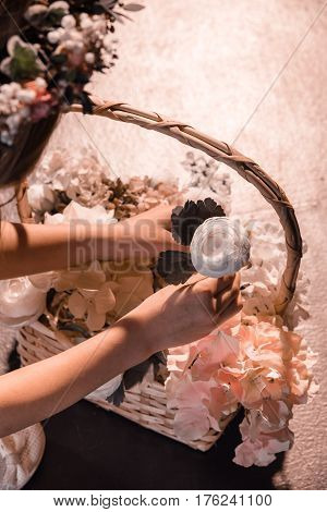 Close-up partial view of girl holding beautiful white flower from basket