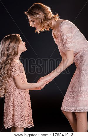 Beautiful Mother And Daughter Holding Hands And Looking At Each Other