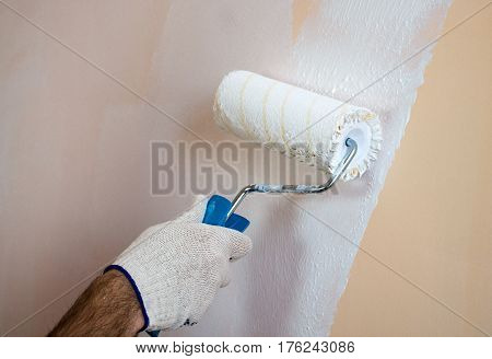 Close up view of man's hand wearing gloves holding paint roller yellow wall painting with white paint