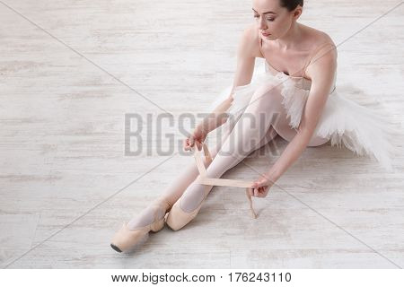 Beautiful young ballerina who puts on pointe shoes at white wooden floor background, top view from above with copy space. Ballet practice. Beautiful slim graceful feet of ballet dancer.