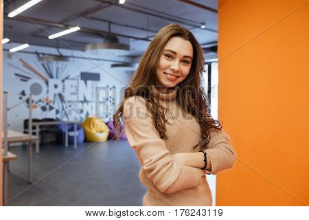 Image of beautiful young lady standing indoors and looking at camera. Coworking.