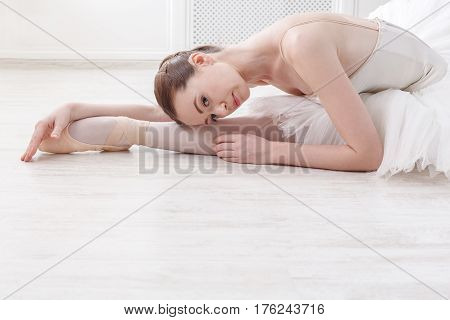 Beautiful graceful young ballerina in pointe shoes at white wooden floor makes ballet leg stretching. Ballet practice of classical dancer.