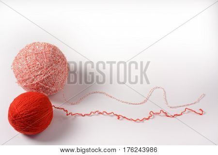 Red and pink tangle of thread for knitting isolated on a white background