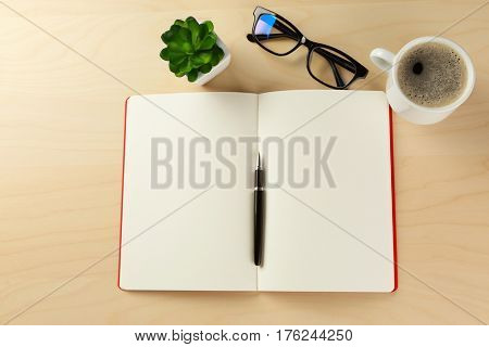 Opened diary, cup of coffee and eyeglasses on wooden table