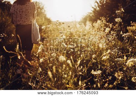 Stylish Hipster Woman With Eco Bag Walking Into Sunlight Among Wildflowers In Summer Evening Field U