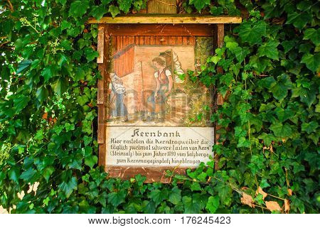 Hallstatt,Austria- August 282015: A painting on a house wall tells the story of the women who carried down salt from the mountains in the 19th century