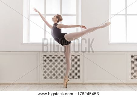 Arabesque. Classical Ballet dancer side view. Beautiful graceful ballerine in black practice ballet position near large window in light hall. Ballet class training, high-key soft toning.