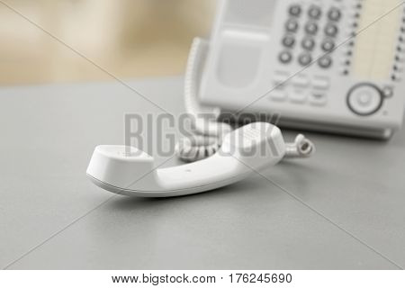 Telephone with picked up receiver on table in office
