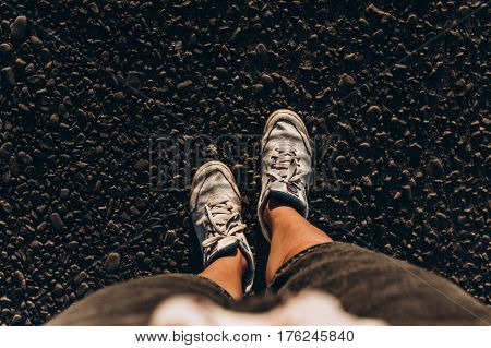 Sneakers On Ground, Woman Taking A Walk On The Summer Road In Sunny Evening. Top View At Legs And Sh