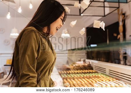 Photo of happy asian young woman standing at the cafe. Looking at sweeties.