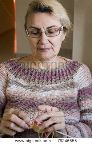 Old Women Looking At Her Hands Holding Knitting Needles And A Yellow Thread In Her Hands To Tie A Sc