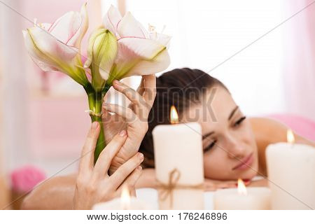 Beutiful woman relaxing after massage in pleasing illuminated room with plants and aroma candles