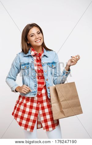 Woman in casual clothes staying on white background holding brown paper bag, smiling at camra