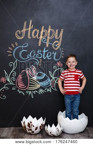 Happy little boy standing inside big cracked eggshell over chalk board with easter doodles background