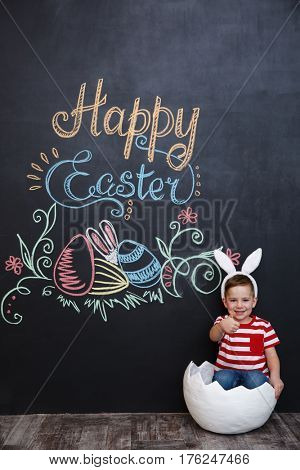 Smiling cute little boy wearing rabbit ears and showing thumbs up gesture while sitting inside big cracked eggshell over chalk board with easter doodles background