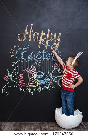 Smiling little boy wearing rabbit ears and standing inside big cracked eggshell pointing at chalk board with easter doodles background
