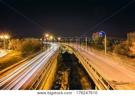Bridge, curve road, night city landscape, freezelight car lights, long exposure, view from above. Night city traffic concept. Voronezh, Dinamo.