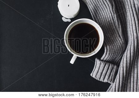Winter cozy concept. Flatlay of gray knitted sweater, candle and coffee drink on black iron table. Warm weekend in cold weather.