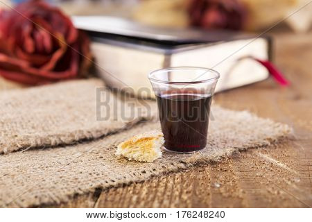 Taking Communion. Cup of glass with red wine bread and Holy Bible on wooden table close-up. Focus on bread.
