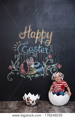 Little cute boy hatching from the egg and sitting inside big cracked eggshell over chalk board with easter doodles background