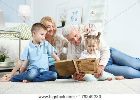 Grandparents looking at photo album with their grandchildren