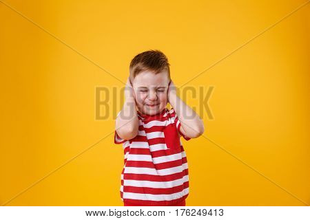 Portrait of an angry unhappy irritated little boy covering ears isolated over orange background
