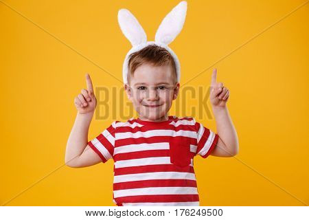 Portrait of a cute little kid wearing bunny ears and poiting two fingers up at copyspace isolated over orange background